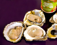 Oysters on a purple background with a Strawberry Abita Beer